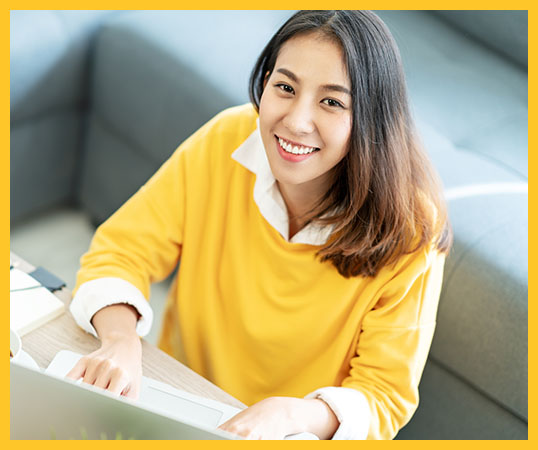 Young attractive happy asian female student sitting at living room floor smiling and looking up at camera working on laptop at home office. Young startup entrepreneur or freelance business concept.