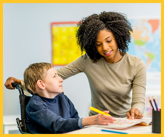 Teacher assisting boy who has a developmental disability