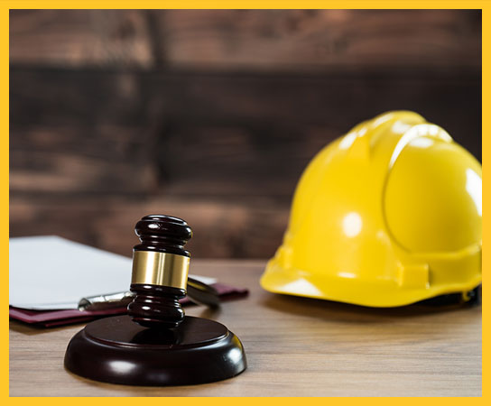 Yellow hardhat and wooden gavel on a legal desk.
