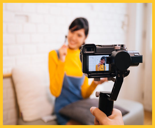 Young Asian woman holding cosmetics brush while recording a video with professional camera