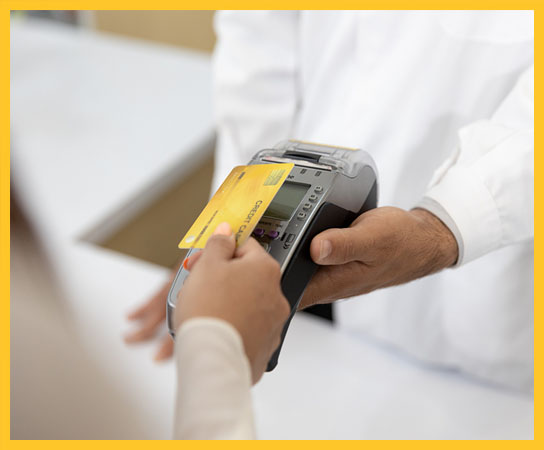 Customer making payment using credit card contactless with a credit card reader machine in modern pharmacy. NFC technology.