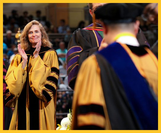 Dr. Pamela Whitten congratulating students during graduation ceremonies.