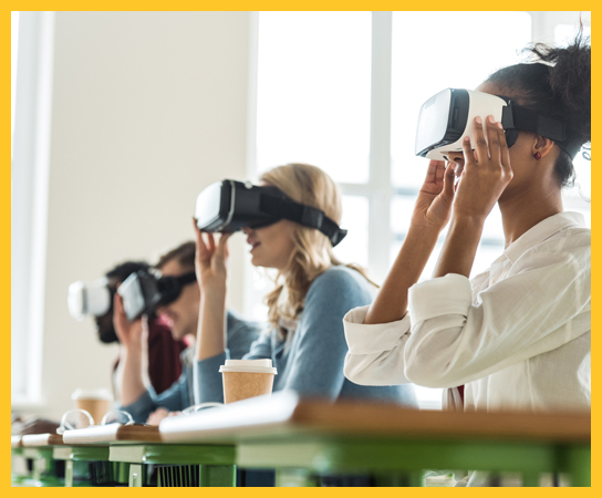 Four graduate students sitting at desks with virtual reality headsets on.