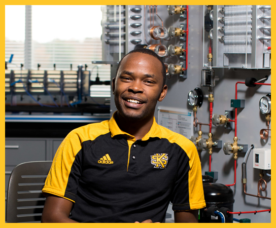 A graduate student, dressed in KSU gear, sitting in front of mechanical and electrical hardware.
