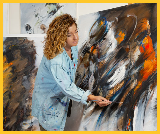 Fine art painter works in her studio, Painted canvases surrounds her.
