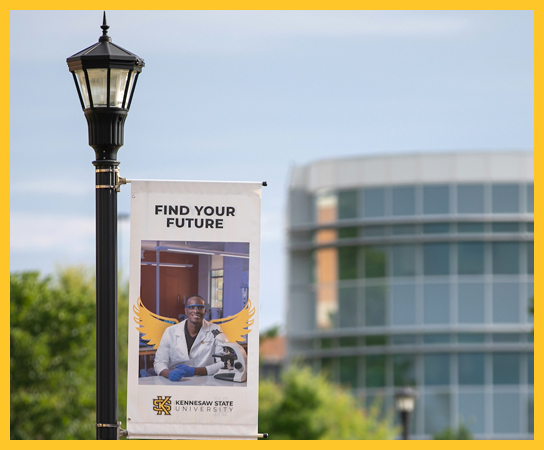 "A KSU ""Find Your Wings"" banner hanging on a street lamp."